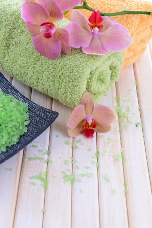 Still life with beautiful blooming orchid flower, towels and bowl with sea salt, on color wooden background photo