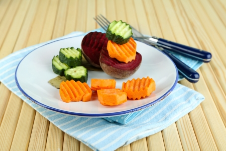 Beautiful sliced vegetables, on plate, on wooden background photo