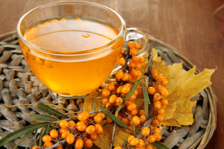buckthorn: Branches of sea buckthorn with jam on wicker stand on wooden background Stock Photo