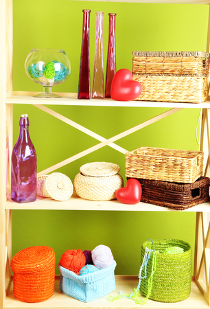 home related: Beautiful white shelves with different home related objects, on color wall background Stock Photo