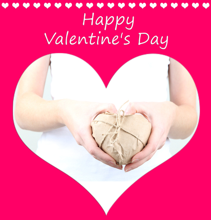 Woman hands holding heart wrapped in brown kraft paper on pink background photo