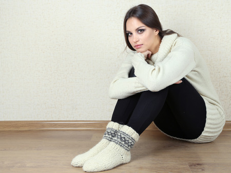 Sad woman sitting on floor near wall Stock Photo - 26397611