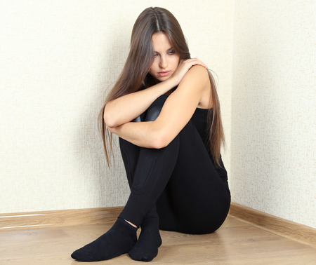 maltreatment: Lonely sad woman sitting on floor near wall Stock Photo