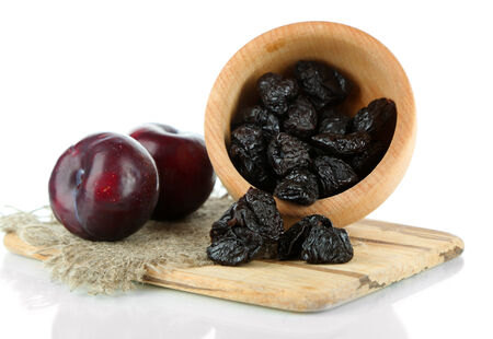 Fresh and dried plums  on wooden board, isolated on white photo