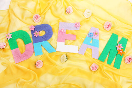 Word Dream created with brightly colored knitting yard on fabric background photo