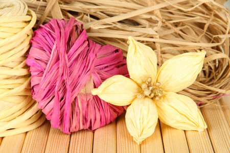 Decorative straw for hand made, flower and heart of straw, on wooden background photo