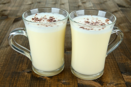 Cups of eggnog on wooden background