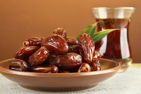 Dried dates on plate with cup of tea on table on brown background