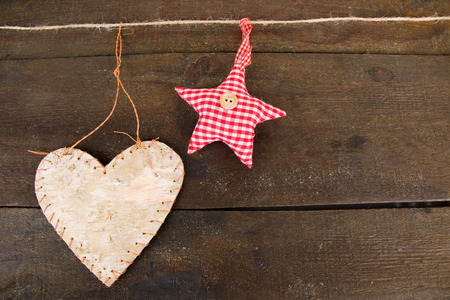 Decorative heart and star on rope, on grey wooden background photo