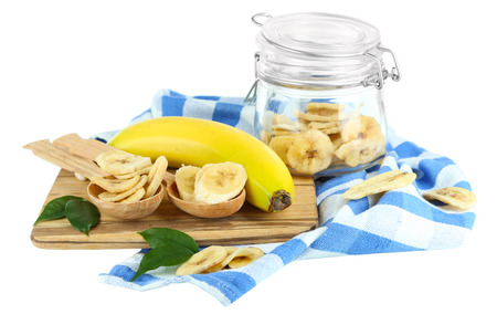 Fresh and dried banana slices in glass jar, on cutting board, isolated on white photo