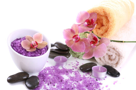 Still life with beautiful blooming orchid flower, towels and bowl with sea salt, isolated on white photo