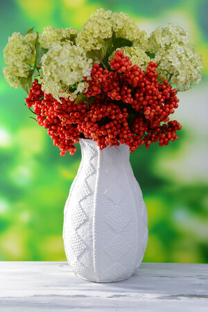 Flowers and berries in vase, on wooden table, on bright background photo