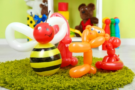 Simple balloon animals and other toys on shelves, on bright background photo