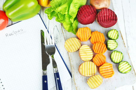 Beautiful sliced vegetables, on cutting board,  on color background photo