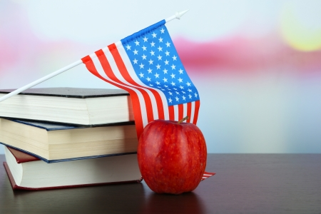 Composition of  American flag, books and apple  on wooden table, on light background photo