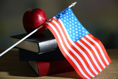 Composition of  American flag, books and apple  on wooden table, on dark background photo