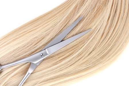 Long blond hair and scissors close up photo