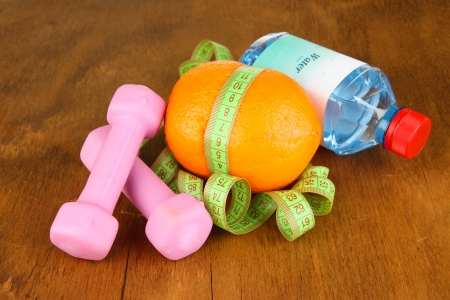 Orange with measuring tape,dumbbells and bottle of water, on wooden background photo