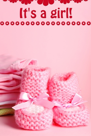 Pile of baby clothes on pink background photo