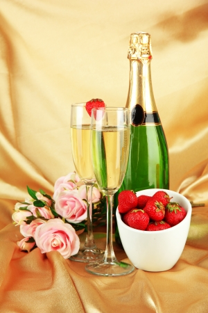 Romantic still life with champagne, strawberry and pink roses, on color fabric background photo