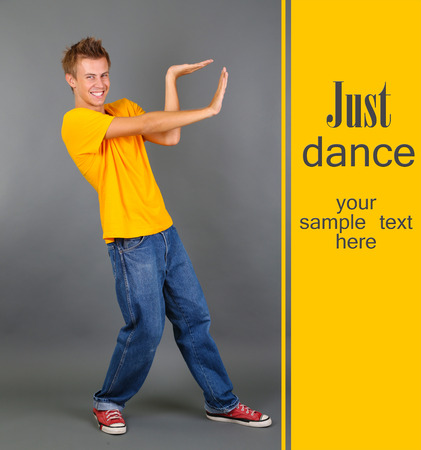 Handsome young man dancing on grey background photo