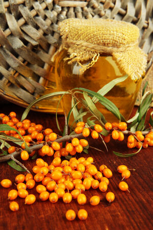 Branch of sea buckthorn with honey on table on wicker background photo