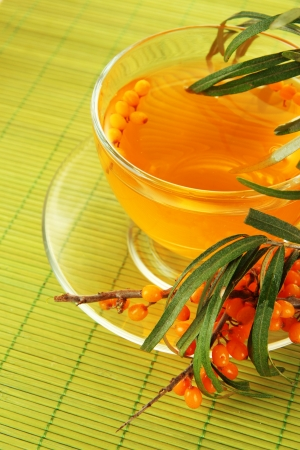 Branches of sea buckthorn with tea on bamboo background photo
