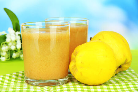 Sweet quince with juice on table on light blue background photo