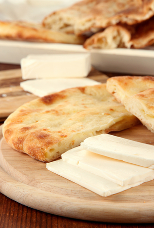 Pita breads with cheese on wooden stands close up photo
