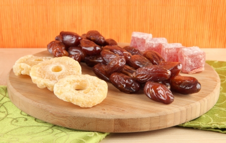 Dried dates with candied pineapples and Turkish delights on table on bamboo background photo