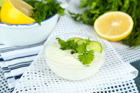 Cucumber yogurt in glass bowl, on color napkin, on wooden  background photo