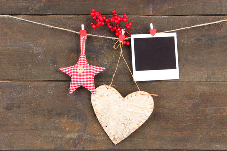Decorative heart, star and empty photo paper on rope, on wooden background photo