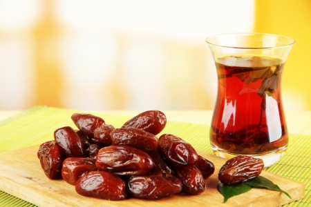 Dried dates with cup of tea on table on bright background