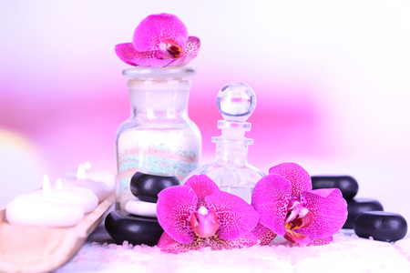 Beautiful spa setting with orchid on white wooden table on bright background photo
