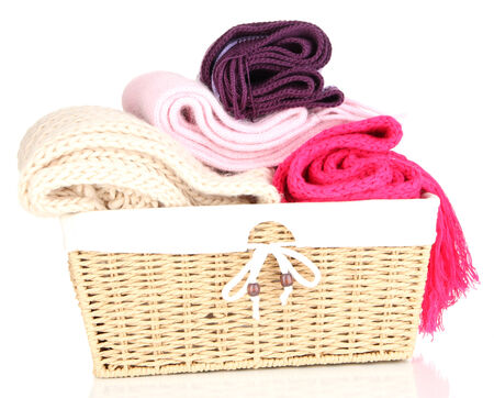 Warm knitted scarves in basket isolated on white photo