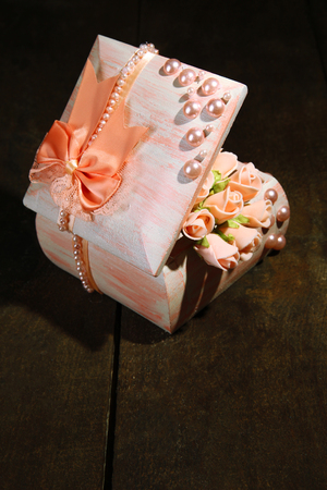 Beautiful hand made casket with roses, on wooden background photo