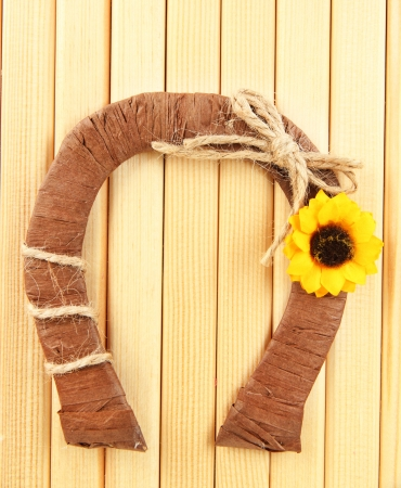 mojo: Decorative horseshoe of straw with sunflower, on wooden background