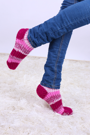 Female legs and  colorful socks on white carpet background photo