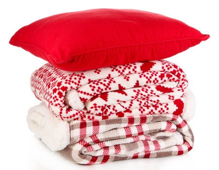 Pile warm plaids and pillow isolated on white photo