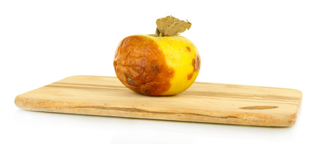 Rotten apple on wooden board isolated on white Stock Photo - 25335078