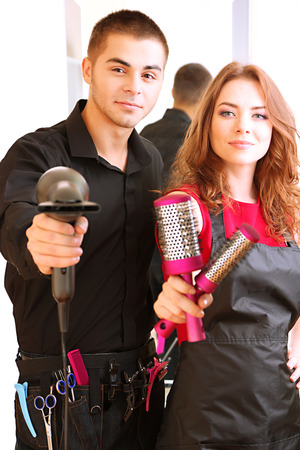 Young man and  woman hairdressers in beauty salon  photo
