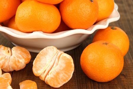 orange peel clove: Mandarini maturi in ciotola su sfondo di legno