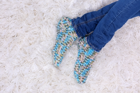 Female legs in blue jeans trousers and  colorful socks on white carpet background photo