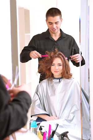 Young man hairdresser do hairstyle girl in beauty salon  photo