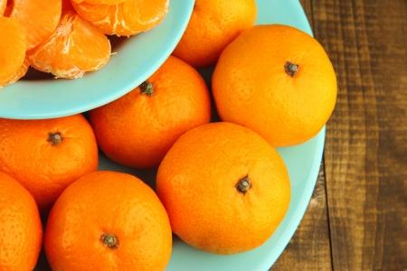 orange peel clove: Mandarini maturi in ciotola su fondo in legno Archivio Fotografico