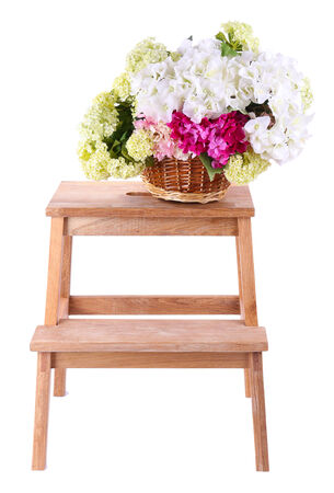 Wicker basket with flowers on small wooden ladder, isolated on white photo