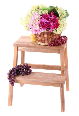 Wicker basket with flowers and fruits,  on small wooden ladder, isolated on white photo