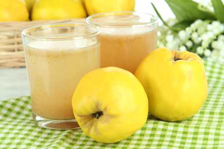 Sweet quince with juice on table close-up photo