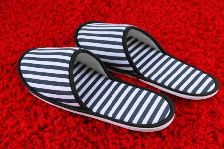 homecoming: Striped slippers on carpet background Stock Photo