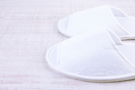White slippers on wooden background photo
